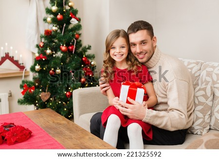 family, christmas, xmas, happiness and people concept - smiling father and daughter holding gift box - stock photo