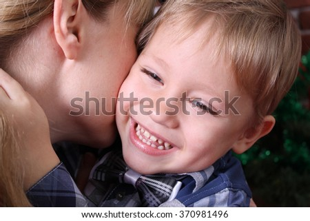 Family concept. A little boy hugs his mother's neck. Happy child. - stock photo