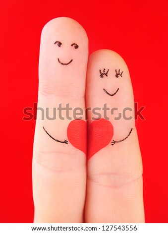 family concept - a man and a woman hold on the red heart, painted at fingers and isolated on red background