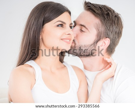 Family concept. Young man kissing his woman tenderly at the cheek, white background.