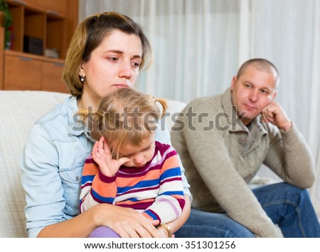 Family conflict. Sad woman with children against husband after quarrel at home