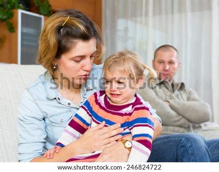 Family conflict. Woman with children against husband after quarrel at home - stock photo