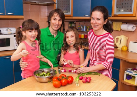 Family cooking at home. Happy smiling parents with kids cook healthy food together at kitchen. Family preparing salad - stock photo