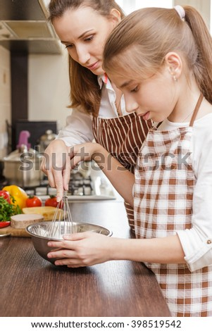 Family cooking background. Mum and daughter whisking eggs at the kitchen  - stock photo