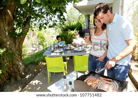 Family cooking meat on barbecue grill - stock photo