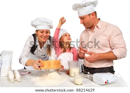 Family cooking  together isolated on white. While mother sifting the flour, father teaching his daughter how to break eggs - stock photo