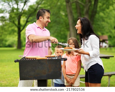 family cookout - dad giving mom food on platter from grill - stock photo