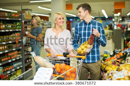 Family couple buying sweet fruits in interior