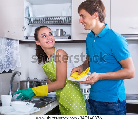 family couple doing and wiping dishes after dinner - stock photo