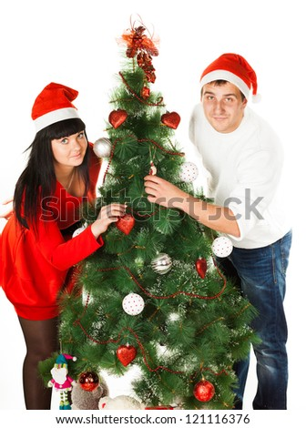 Family couple in red Santa's caps decorating Christmas tree