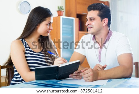 Family couple making list of purchases and discussing plans