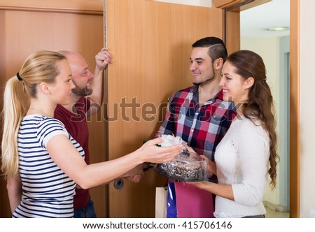 Family couple receiving visitors with a gifts at the home