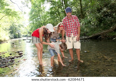 Family crossing a river - stock photo