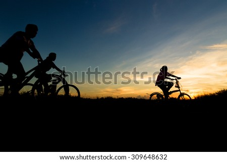 Family cycling exercise during sunset. - stock photo