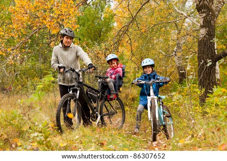 Family cycling outdoors, golden autumn in park - stock photo