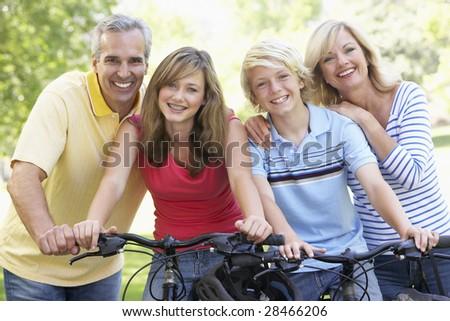 Family Cycling Through A Park - stock photo