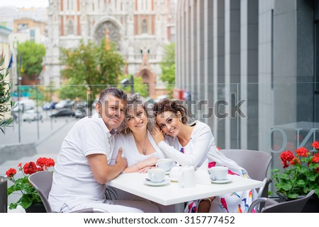 Family day. Elderly loving couple and their adult daughter smiling at camera while sitting in sidewalk cafe. - stock photo