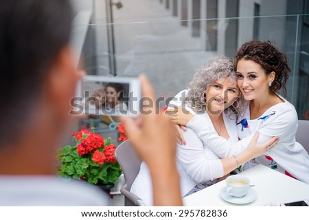 Family day. Middle aged woman and her adult daughter embracing in cafe while father photographing them on smartphone. - stock photo