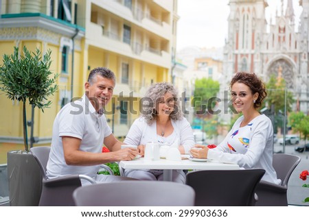 Family day. Senior couple and their adult daughter sitting in sidewalk cafe. - stock photo