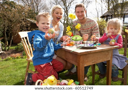 Family Decorating Easter Eggs On Table Outdoors - stock photo