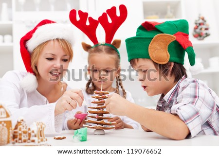 Family decorating the gingerbread christmas tree together - focus on the boy - stock photo