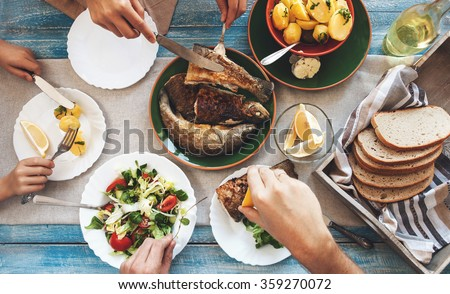 Family dinner with fried fish, potato and salad - stock photo