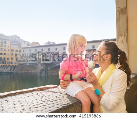 Family discovering old Italian treasures in Florence. Happy mother and daughter eating ice cream near Ponte Vecchio - stock photo