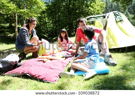 Family doing camping in the forest - stock photo
