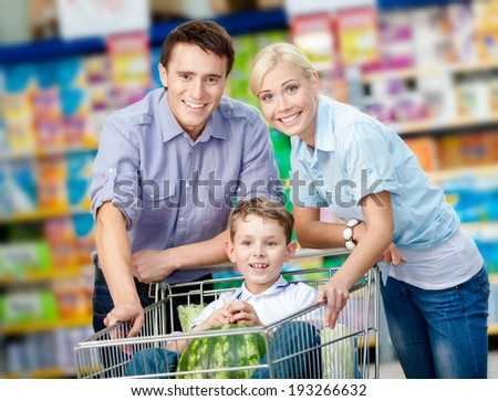 Family drives shopping trolley with food and boy sitting there with watermelon. Concept of fresh and healthy food and consumerism - stock photo