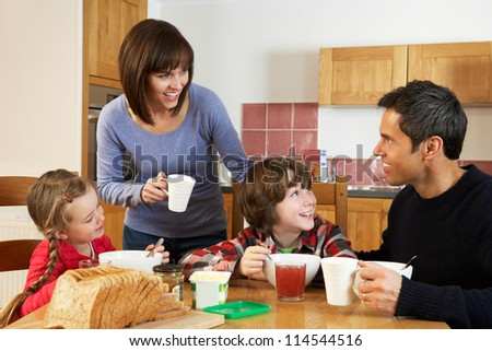 Family Eating Breakfast Together In Kitchen - stock photo