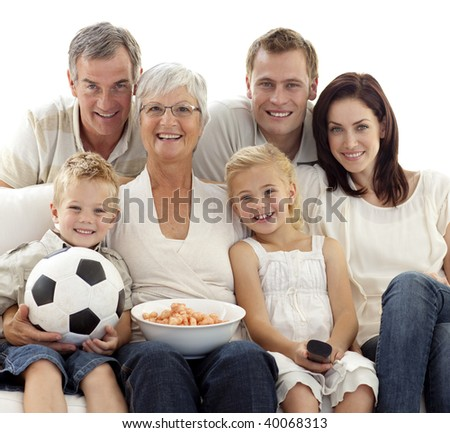 Family eating crisps and watching a football match at home - stock photo