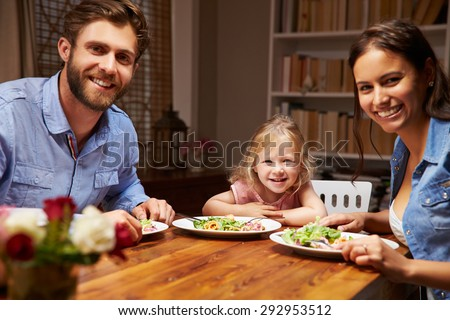 Family eating dinner at a dining table, looking at camera - stock photo