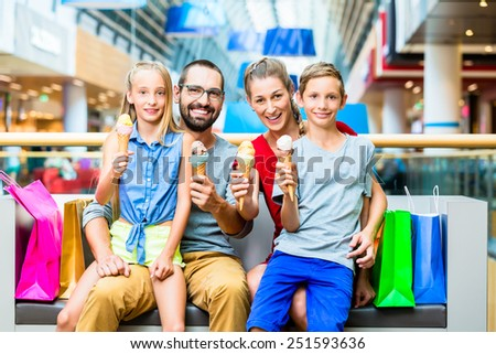 Family eating ice cream in shopping mall with bags - stock photo