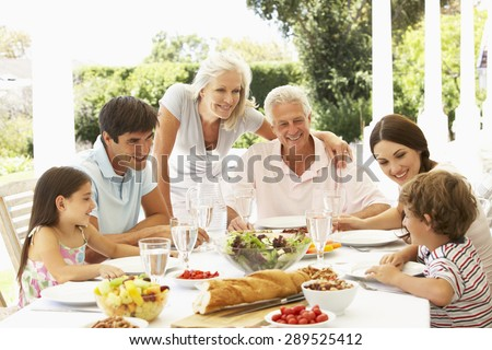 Family eating lunch outside in garden - stock photo