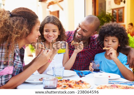 Family Eating Meal At Outdoor Restaurant Together - stock photo