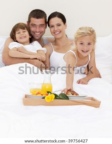 Family eating nutritive breakfast in bedroom - stock photo