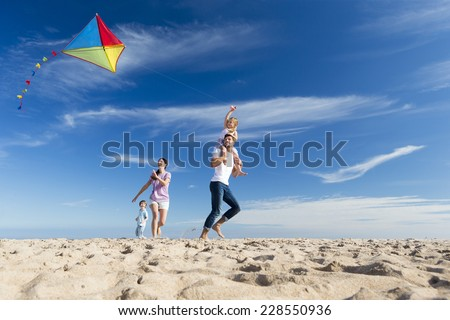 Family Enjoying a Day on the Beach Flying a Kite - stock photo