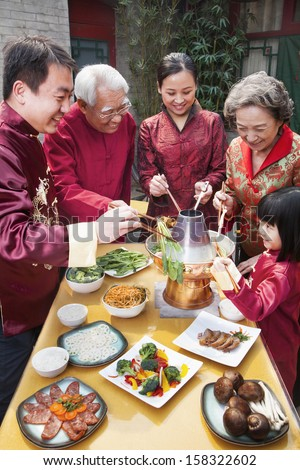 Family enjoying Chinese meal in traditional Chinese clothing - stock photo