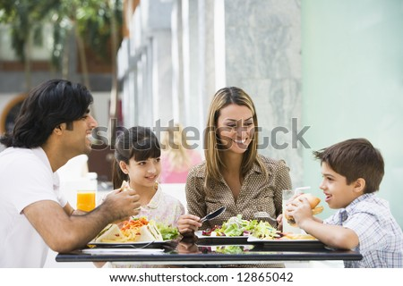 Family enjoying meal sitting at cafe table - stock photo