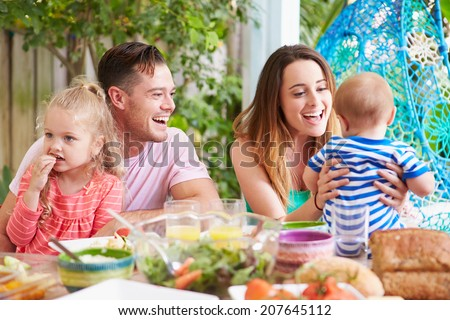 Family Enjoying Outdoor Meal At Home - stock photo