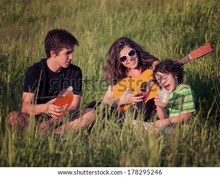 Family enjoying the nice summer weather outdoors in a park. Image has effects applied for certain mood - stock photo