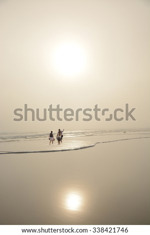 Family enjoying time together on beautiful foggy beach early morning in Daytona Beach, Florida. - stock photo