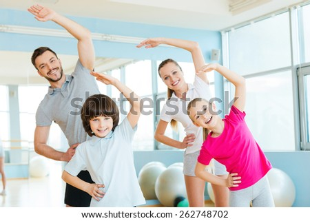 Family exercising. Happy sporty family doing stretching exercises in sports club  - stock photo