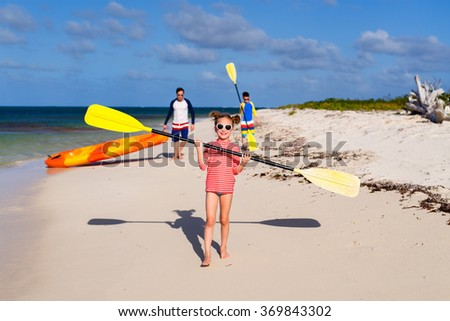 Family father and kids pulling colorful kayaks after paddling at tropical ocean water during summer vacation - stock photo