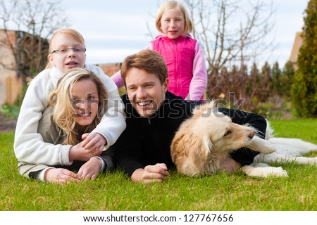 Family, father, mother and daughters, sitting together with their dog on a meadow, they laugh and have fun - stock photo