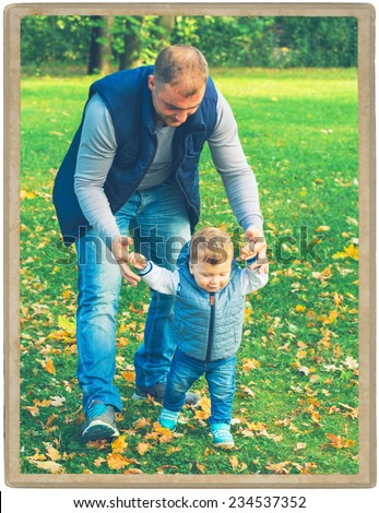 Family father  with child in park walking in same clothes textile jeans jacket. First step baby   - stock photo