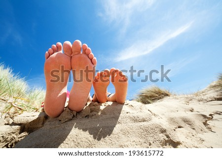 Family feet relaxing and sunbathing on the beach concept for vacation and summer holiday - stock photo