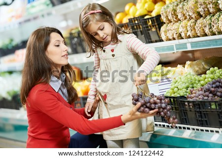 Family food shopping. Young woman mother and little girl daughter choosing fruits grape in supermarket - stock photo