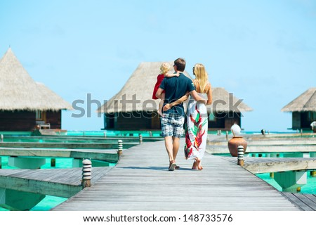 Family from back view having tropical vacation at Maldives, walking towards water bungalows - stock photo