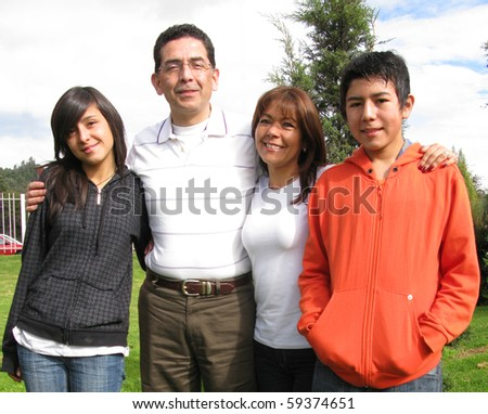 Family from four stands on grass against house